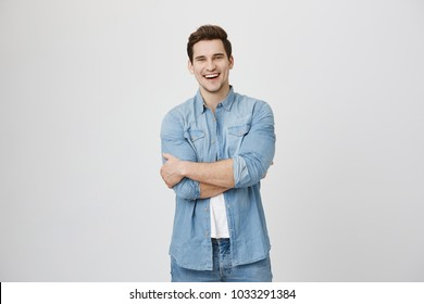 Portrait of guy wearing denim shirt, standing with crossed hands while laughing, isolated over white background. Attractive hairdresser greets new visitor offering him cup of coffee