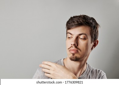 Portrait of a guy who brushes something off his shoulder. puzzled emotion. studio shot. copy space. gesturing concept. isolated over grey background. dressed casual clothes. tiny beard and mustache.