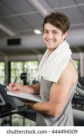 Portrait of gym instructor writing on clipboard at gym