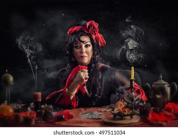 Portrait of gypsy witch doing deadly curse ritual with a knife and playing cards. Mature sorceress wearing red-black dress sits at the desk surrounded smoking candles on black grange background.