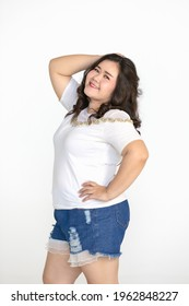 Portrait half body shot of Asian young happy cute friendly overweight fat teen long black hair female wears white shirt and short blue jeans stand smiling look at camera against white background.
