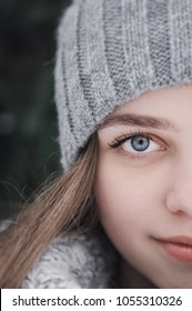 Portrait with half of the face. Female teenager with beautiful blue eyes and long hair in warm woolen hat and scarf of gray color