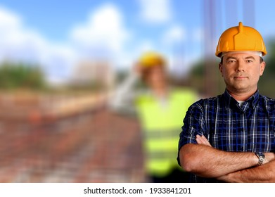 Portrait of half face of a handsome young man in casque at construction site and smiling.
