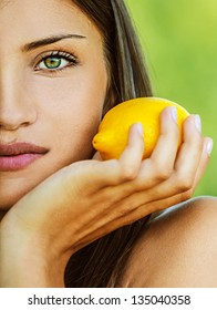 Portrait half of face young beautiful woman with bare shoulders holding lemon yellow, on green background summer nature.