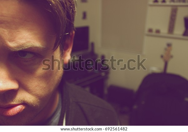 Portrait of half a mans concerned face. Bedroom in the background
