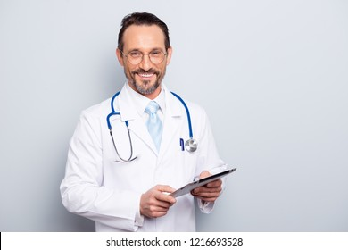 Portrait of half turn brunet hair bristle pharmacist man look at camera stand isolated on light gray background half turn make beaming toothy smile hold tablet in hands