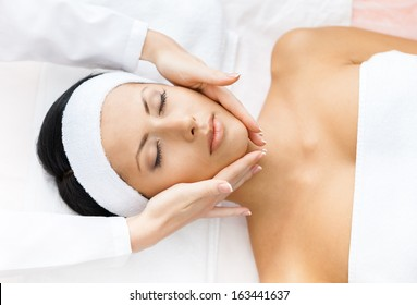 Portrait of half-naked woman with closed eyes getting face massage. Concept of relax and medicine