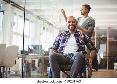 Portrait of handicap businessman with colleague in background at creative office