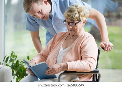 Portrait of handicapped senior woman reading book