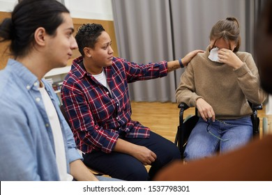 Portrait of handicapped young woman crying sitting in wheelchair with friend comforting her during support group meeting, copy space