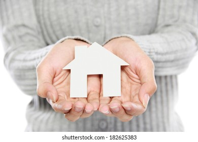 portrait of Hands of woman holding white paper house