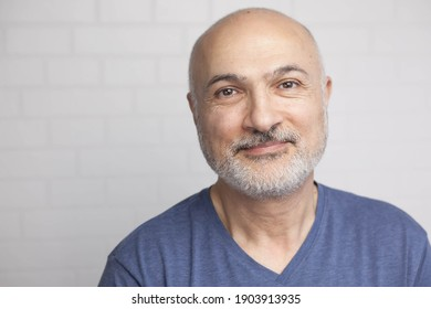 Portrait of a handsome 50 years old man with unshaven hair in a blue t-shirt indoors.