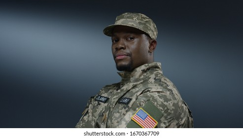 Portrait of the handsome African american male soldier in the uniform of US forces and hat looking with a serious face straight at the camera.