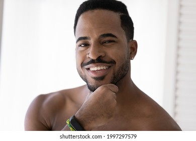 Portrait of handsome African American man with stylish beard touching stubble, applying aftershave balm, looking at camera with toothy smile. Metrosexual, male beauty care concept. Head shot