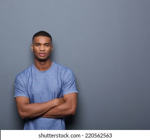 Portrait of a handsome african american man posing with arms crossed on gray background