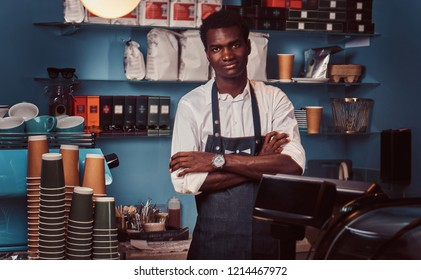 Portrait of a handsome African barista at counter of a trendy coffee shop.