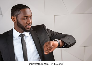 Portrait of handsome afro american businessman. Young stylish businessman looking at watch. Man wearing suit and tie