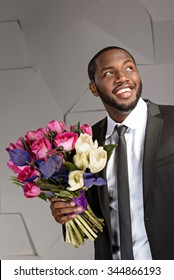 Portrait of handsome afro american man. Young stylish businessman smiling and holding nice bouquet of flowers. Man wearing suit and tie