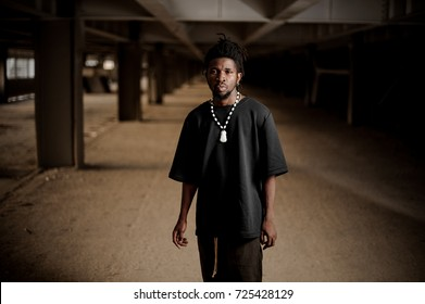 Portrait of the handsome afro american man with dreadlocks and dressed in trendy black clothes