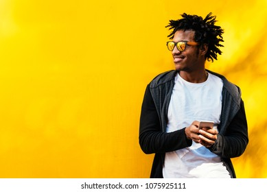 Portrait of handsome afro man using his mobile in the street.