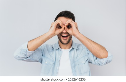 Portrait of handsome amazed male wearing blue shirt and white T-shirt holding his hands at his eyes as if looking through binoculars or glasses, surprised happily against studio light wall background