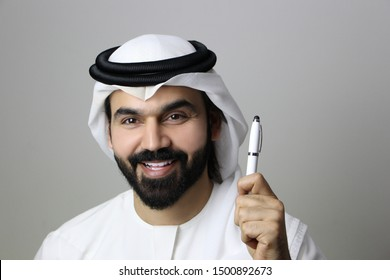 Portrait Of A Handsome Arab Businessman/Student Smiling Holding A Pen And Wearing UAE Emirati Dress