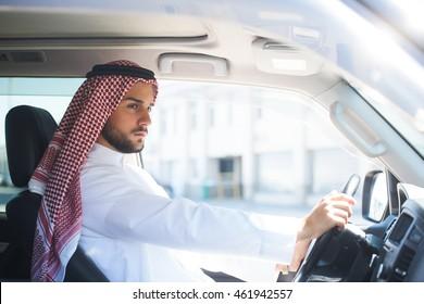 Portrait of a handsome arabian man driving a car