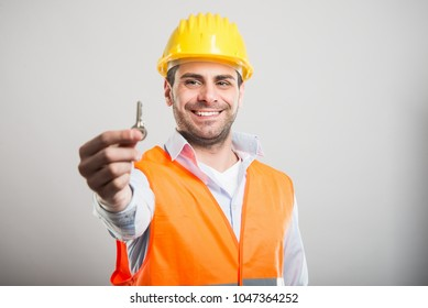 Portrait of handsome architect holding house key and smiling on gray background