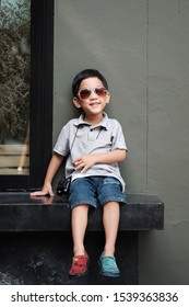 Portrait handsome Asian boy 5 year old wear sun glasses and binoculars. Asia boy smile and sitting on bench, Kid posting relax activity. Concept summer and holiday. Fashion kid. hipster kid lifestyle.