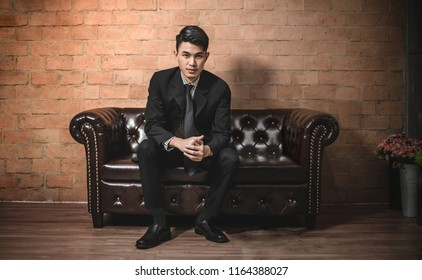 Portrait of a handsome Asian businessman in black suit  on a luxury vintage leather sofa