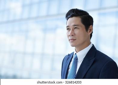 Portrait of handsome Asian businessman looking away