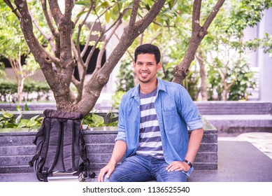 Portrait of handsome asian college student smiling guy sitting on the park relaxed after class.
