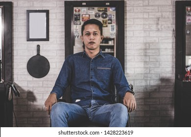 Portrait of handsome Asian man with blue jeans shirt sitting at barbershop chair