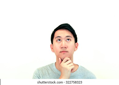 Portrait of Handsome Asian man thinking and looking up on isolated white background with copy space. Human face expressions, emotions, feelings, body language, perception