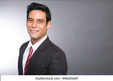 portrait of a handsome asian men in a suit smiling