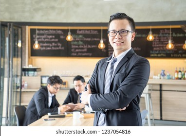 Portrait of handsome Asian young man in formal black suite, wearing eyeglasses, proudly smiling, standing in front of coffee shop.  Young startup Coffee business concept.