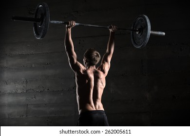 Portrait of a handsome athlete from behind. Athlete raises the barbell over your head. Studio shots in the dark tone.