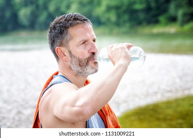 portrait of handsome athlete standing outdoors and drinking from bottle