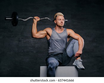 Portrait of a handsome, athletic blond male sits on a white box and holds barbell on his shoulder.