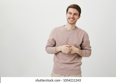 Portrait of handsome athletic male with charming smile holding hands near chest, standing in casual post as if talking over gray background. Seductive man having conversation with girl he likes
