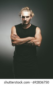 Portrait of a handsome athletic man posing over grunge background. Urban style.