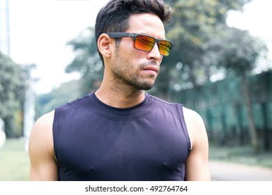 portrait of a handsome athletic man wearing  shades on a outdoor park, after exercise