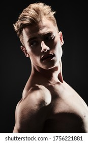 Portrait of a handsome athletic muscular man on a black background. Man's beauty and health. Sports concept.