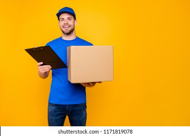 Portrait of handsome attractive cheerful bearded mailman, postman in blue uniform holding big cardboard box and clipboard on-time, isolated over bright vivid yellow background, copy-space