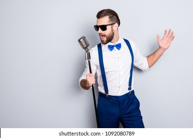 Portrait of handsome attractive singer in blue pants with suspenders and black glasses, singing hit with open mouth in microphone gesture with hand isolated on grey background