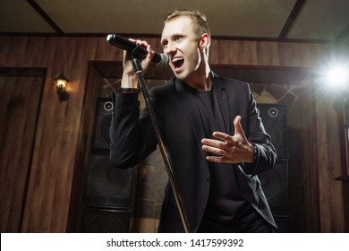 Portrait of handsome attractive singer singing hit with open mouth in microphone