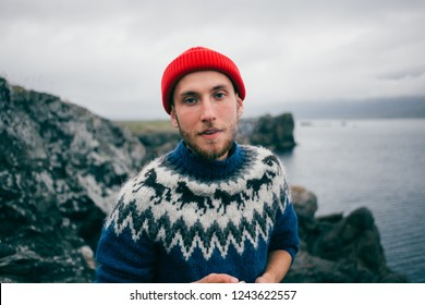Portrait of handsome attractive young bearded man smoking cigarette, blowing smoke in raw and rough environment in mountains, wears hipster authentic blue wool sweater, looks at camera and smiles
