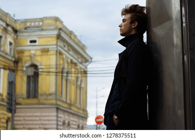 Portrait of a handsome, attractive, young man in a blue suit, coat, in the city. pensive and sad, waiting. businessman. watch on hand