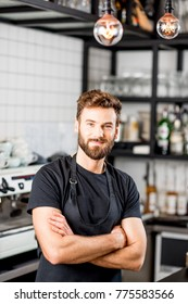 Portrait of a handsome barista in black t-shirt and apron standing at the bar of the modern cafe