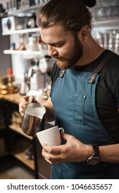 Portrait of a handsome barista making a cup of coffee at the coffee shop
